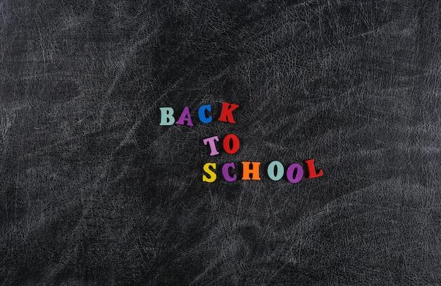 Tekst z powrotem do szkoły z kolorowych liter na tle tablicy kredowej.