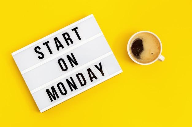 """Tekst """"zacznij w poniedziałek"""" na lightboxie i filiżance kawy. koncepcja nowych początków. początek tygodnia roboczego."""