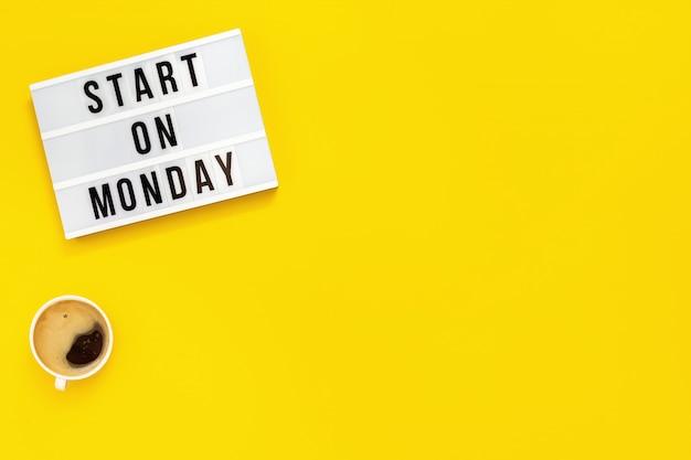 """Tekst """"zacznij w poniedziałek"""" na lightboxie i filiżance kawy. początek tygodnia roboczego. widok z góry na żółtym tle."""