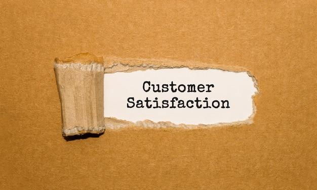 Tekst zadowolenie klienta widoczny za podartym brązowym papierem