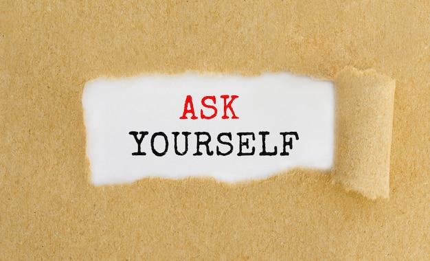 """Tekst """"zapytaj siebie"""" pojawiający się za podartym brązowym papierem."""