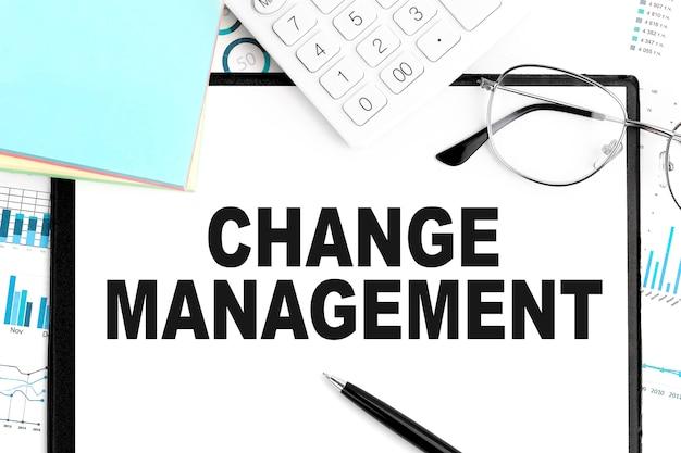 Tekst zarządzanie zmianami na schowku, długopisie, okularach, kalkulatorze, naklejce, wykresach. pomysł na biznes. leżał płasko.