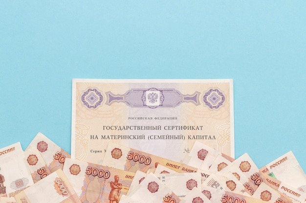 Tekst zaświadczenie federacji rosyjskiej potwierdzające macierzyński kapitał rodzinny i dużo banknotów. pomoc państwa dla rodziny przy urodzeniu drugiego dziecka.