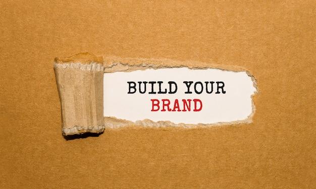 Tekst zbuduj swoją markę znajdujący się za podartym brązowym papierem