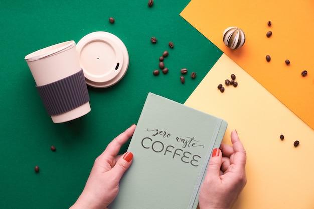 """Tekst """"zero odpadów kawy"""" na notatniku w rękach. zero marnowania kawy. ekologiczne kubki do kawy wielokrotnego użytku w rękach, geometryczny widok z góry na podzielonym papierze w odcieniach zieleni, żółci i pomarańczy."""