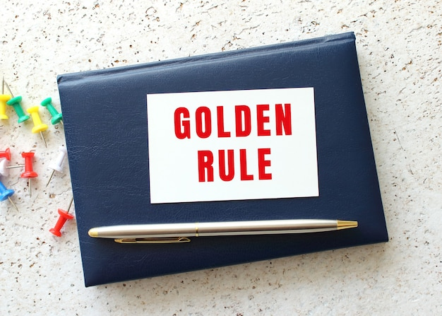 Tekst złota zasady na wizytówce leżącej na niebieskim notesie obok pióra. pomysł na biznes.