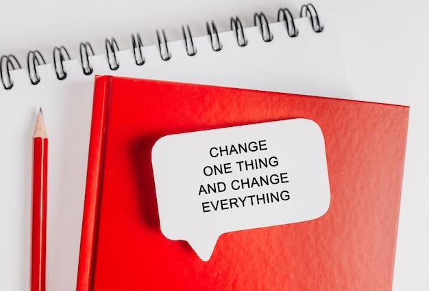Tekst zmień jedną rzecz i zmień wszystko na białej naklejce na czerwonym notatniku z tłem biurowym. mieszkanie leżało na koncepcji biznesu, finansów i rozwoju