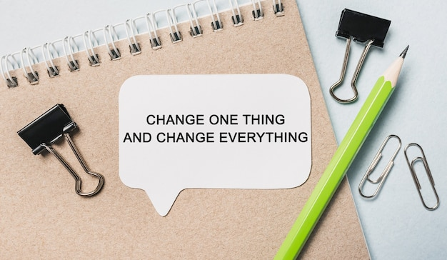 Tekst zmień jedną rzecz i zmień wszystko na białej naklejce z tłem biurowym. mieszkanie leżało na koncepcji biznesu, finansów i rozwoju