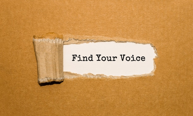 Tekst znajdź swój głos pojawiający się za podartym brązowym papierem