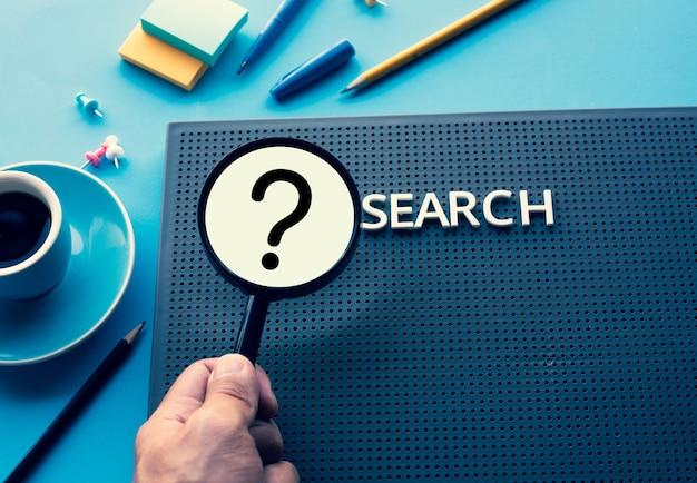 Tekst znaku zapytania wyszukiwania z lupą na stole na biurku edukacja biznesowa