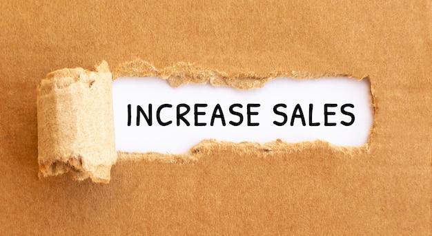 Tekst zwiększa sprzedaż, który pojawia się za podartym brązowym papierem.