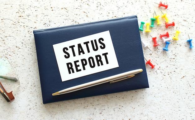 Tekstowy raport o stanie na wizytówce leżącej na niebieskim notatniku obok okularów