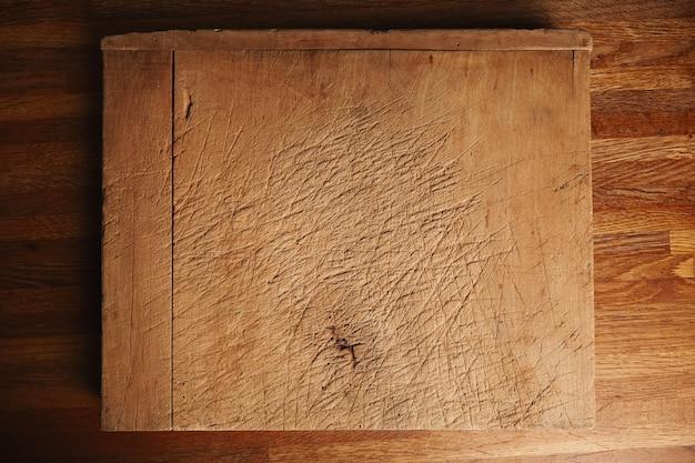 Tekstura bardzo starej i mocno używanej deski do krojenia z głębokimi cięciami na pięknym brązowym drewnianym stole