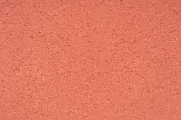 Tekstura betonowej ściany pokryta jest dekoracyjnym tynkiem o szorstkiej powierzchni i pęknięciami w kolorze koralowca