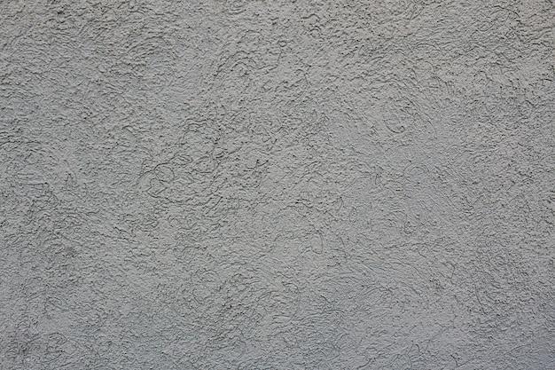 Tekstura betonowej ściany z falistą powierzchnią w kolorze szarym
