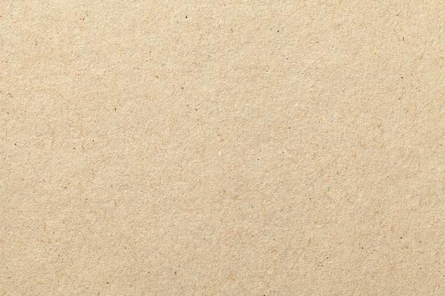 Tekstura beżowego starego papieru rzemieślniczego, zmięte tło.