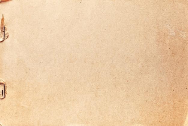 Tekstura beżowego starego papieru z klipsem rdzy, zmięte tło.
