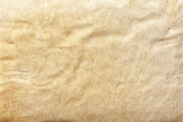 Tekstura beżowego starego papieru, zmięte tło. tło powierzchni grunge brązowy vintage. struktura tektury pergaminowej.