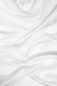 Tekstura białej tkaniny jedwabnej, tło tekstylne, draperia i plisy na delikatnej tkaninie. ostre światło i widok z góry.