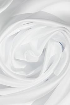 Tekstura białej tkaniny jedwabnej, tło tekstylne, draperia i plisy na delikatnej tkaninie.