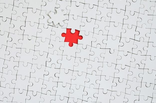Tekstura białej układanki w stanie złożonym z jednym brakującym elementem tworzącym czerwoną przestrzeń