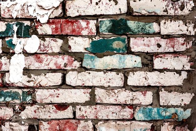 Tekstura ceglanego muru z pęknięciami i zadrapaniami