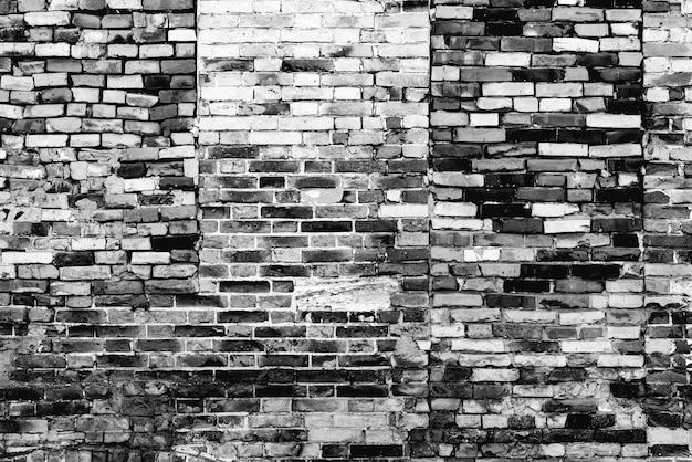 Tekstura ceglanego muru z pęknięciami i zarysowaniami w tle
