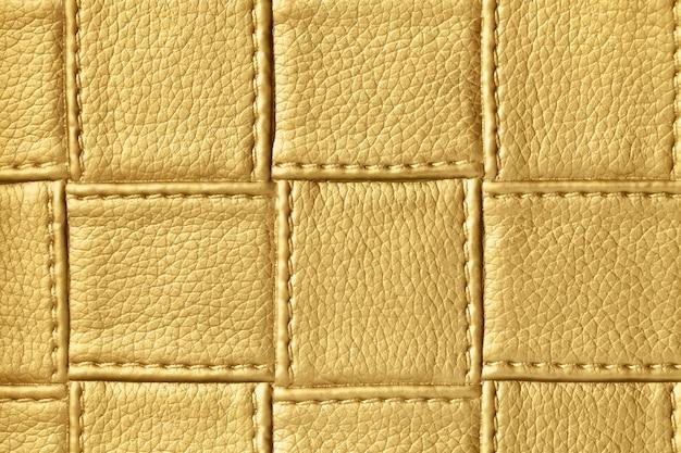 Tekstura ciemnej złotej i żółtej skóry z kwadratowym wzorem i ściegiem, makro.
