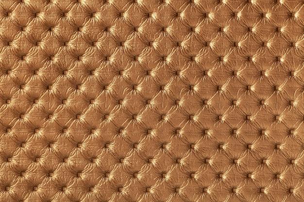 Tekstura ciemnobrązowej skóry z wzorem capitone, makro.