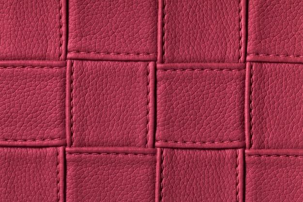 Tekstura ciemnofioletowe skórzane tło z kwadratowym wzorem i ściegiem.