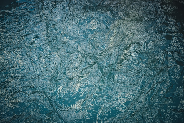 Tekstura ciemnoniebieskie spokojne wody jeziora. medytacyjne fale na powierzchni wody. natura minimalne tło ciemnozielone jezioro. naturalne tło jasnej ciemnej turkusowej wody. pełna klatka fragmentu jeziora.