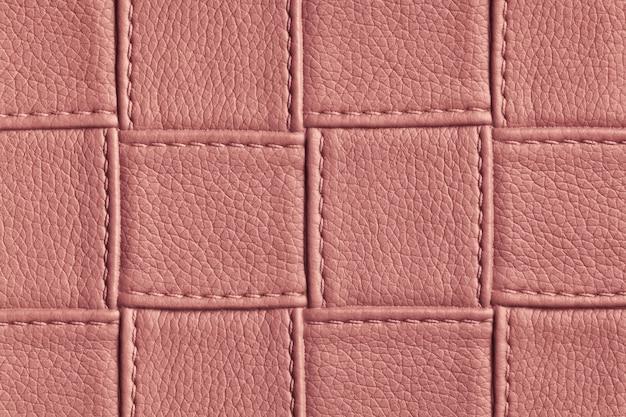 Tekstura ciemnoróżowe i różowe tło skóry z kwadratowym wzorem i ściegiem