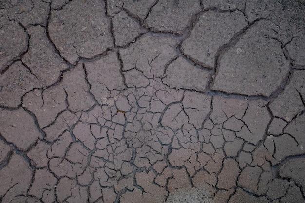 Tekstura czarnej popękanej suszonej gleby.