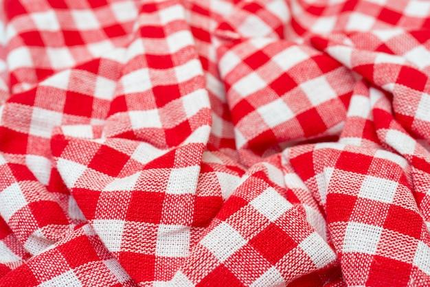 Tekstura czerwonego materiału. ręcznik kuchenny w kratkę czerwony. piękne ozdobne fałdy.