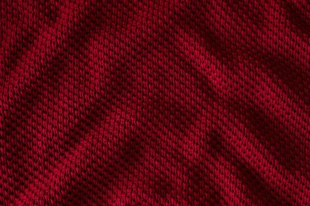 Tekstura czerwonego swetra z dzianiny zbliżenie bordowego tła
