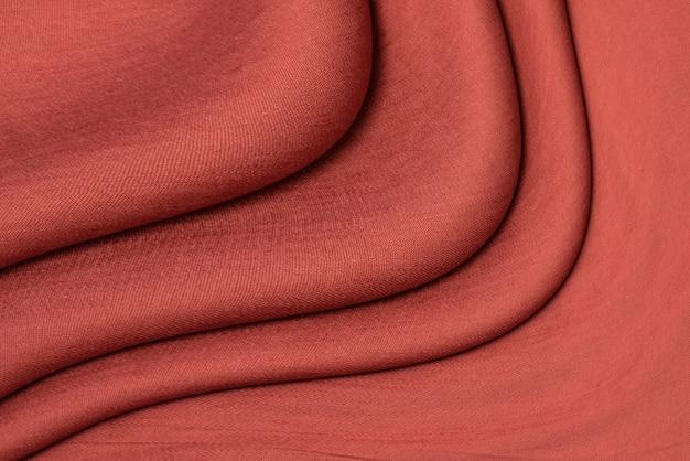 Tekstura czerwonej tkaniny lnianej z bliska ciemnoczerwony kolor. teksturowane streszczenie tło czerwone, widok z góry