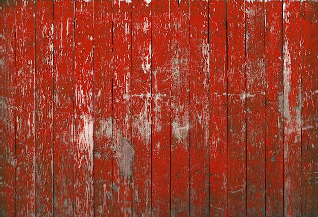 Tekstura drewna na czerwonym tle. starodawny stary płot z łuszczącą się farbą czerwoną.
