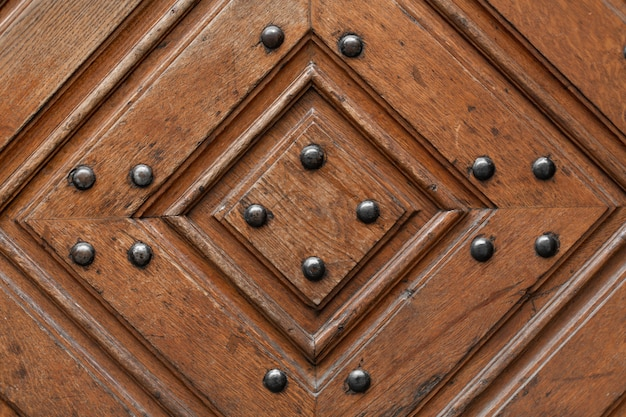 Tekstura drewniane drzwi z metalowymi nitami. wzór diamentu z drewna