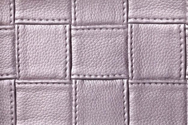 Tekstura fioletowej skóry z kwadratowym wzorem i ściegiem