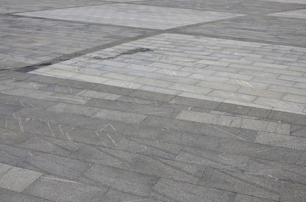 Tekstura granitowych płytek chodnikowych z różnych kwadratowych platform w jasnym świetle słonecznym