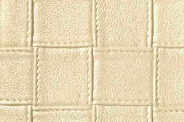 Tekstura jasnozłotej i kremowej skóry z kwadratowym wzorem i ściegiem
