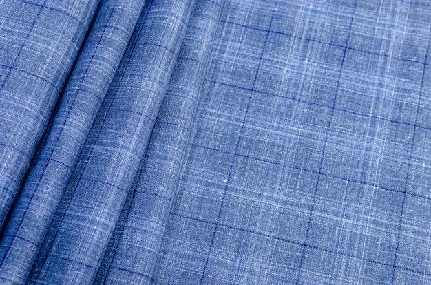 Tekstura jedwabnej tkaniny w niebiesko-niebieską kratkę. tło, wzór