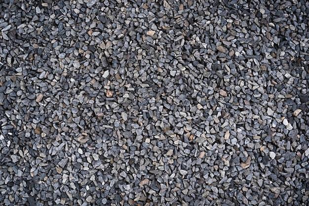 Tekstura kamieni na ziemi szare kamyczki. kamienne tło