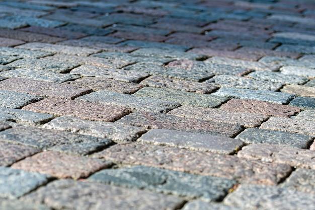 Tekstura kamiennego chodnika, granitowe brukowane tło chodnika, abstrakcyjne tło z bliska stary bruk brukowiec