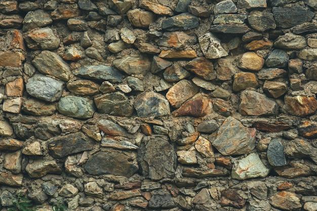 Tekstura kamiennego muru. stary zamek kamienny mur tekstura tło. kamienny mur jako tło lub tekstura. część kamiennej ściany, na tło lub teksturę