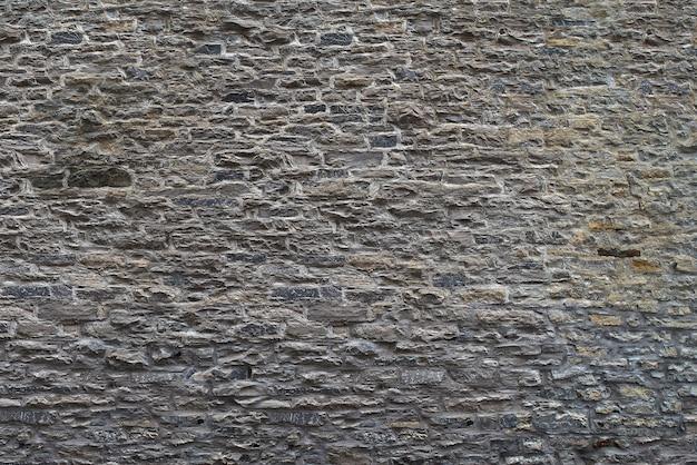 Tekstura kamiennej ściany. stary grodowy kamiennej ściany tło. ściana wykonana z dzikiego kamienia. naturalne tło