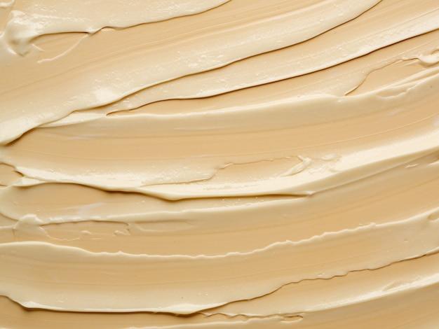 Tekstura kremu nude na beżowym tle. zbiory fotografii