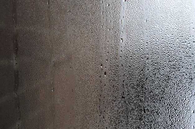 Tekstura kropla deszcz na szklanym mokrym przejrzystym tle. stonowany w kolorze szarym