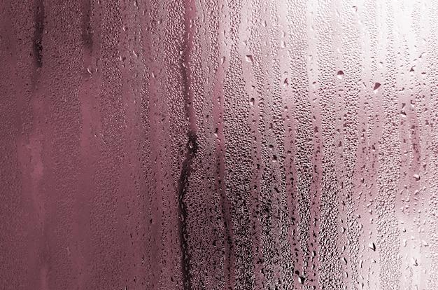 Tekstura kropla deszcz na szklanym mokrym przejrzystym tle. stonowany w różowym kolorze