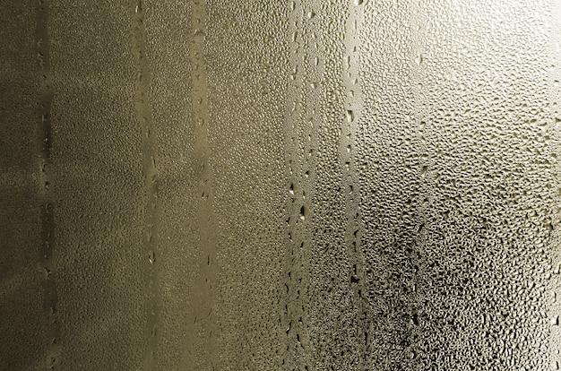 Tekstura kropla deszczu na szklanym mokrym przejrzystym tle. stonowany w żółtym kolorze